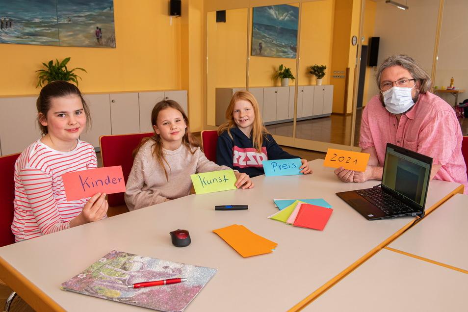 Ralph Torsten Lincke und die Jurymitglieder Emilia, Jolien und Lena (von links) bewerten Beiträge für den sächsischen Kinderkunstpreis.