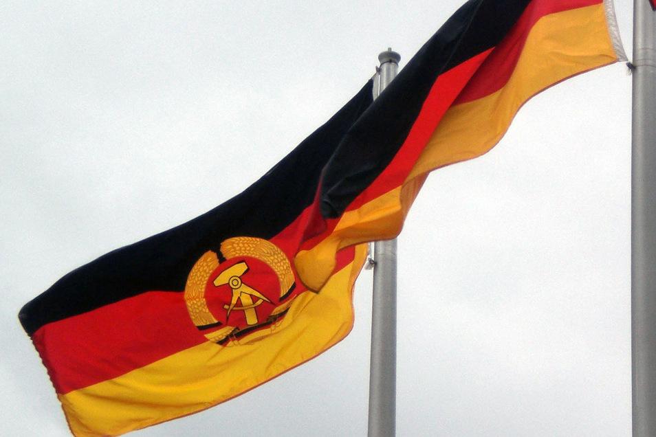 Die Flagge der ehemaligen DDR und die bundesdeutsche Fahne: Wie sehr wirkt sich das Erbe der DDR auf die heutige Gesellschaft aus? Darum geht es beim 31. Bautzen-Forum.