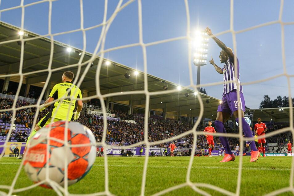 Hamburgs Torwart Daniel Heuer Fernandes (l) kann das Tor zum 1:0 nicht verhindern während Aues Babacar Gueye (r) jubelt.
