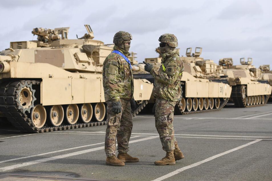 """Ketten- und Radfahrzeuge der US-Armee werden im Rahmen Großübung """"Defender Europe 20"""" in Bremerhaven ausgeladen und von zwei US-Soldaten bewacht."""