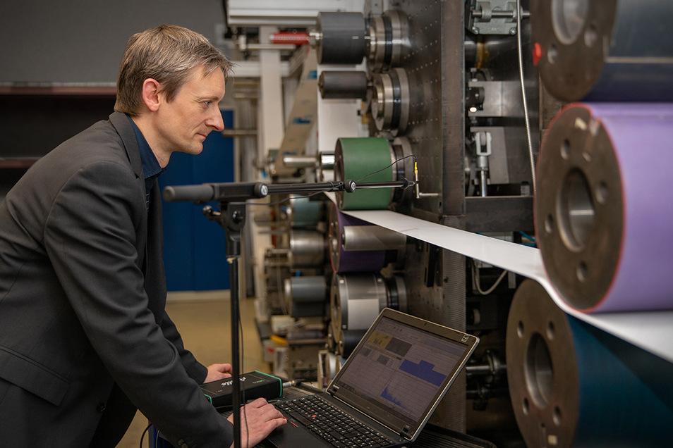 Projektleiter Georg Schmidt prüft an einer Rolle-zu-Rolle-Druckmaschine die Papierlautsprecherbahn akustisch und kann so deren Qualität beurteilen.