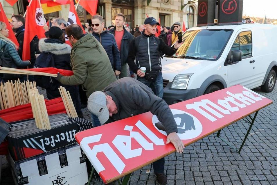 """Ein Biertisch mit demTransparent mit """"Heil Merkel"""" wird aufgestellt."""
