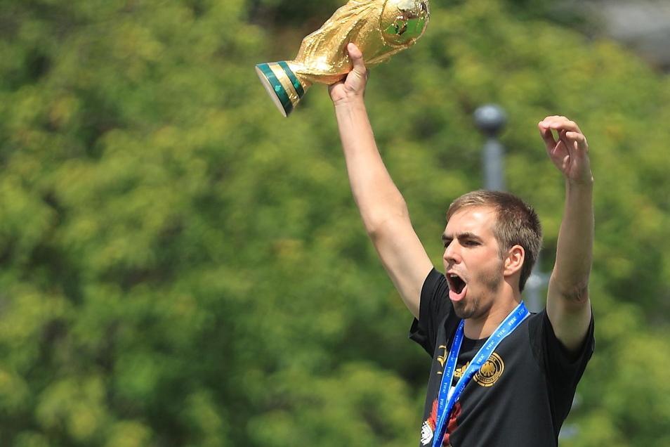 Philipp Lahm jubelt am 15.07.2014 beim Empfang der Fußball-Nationalmannschaft in Berlin mit dem WM-Pokal.