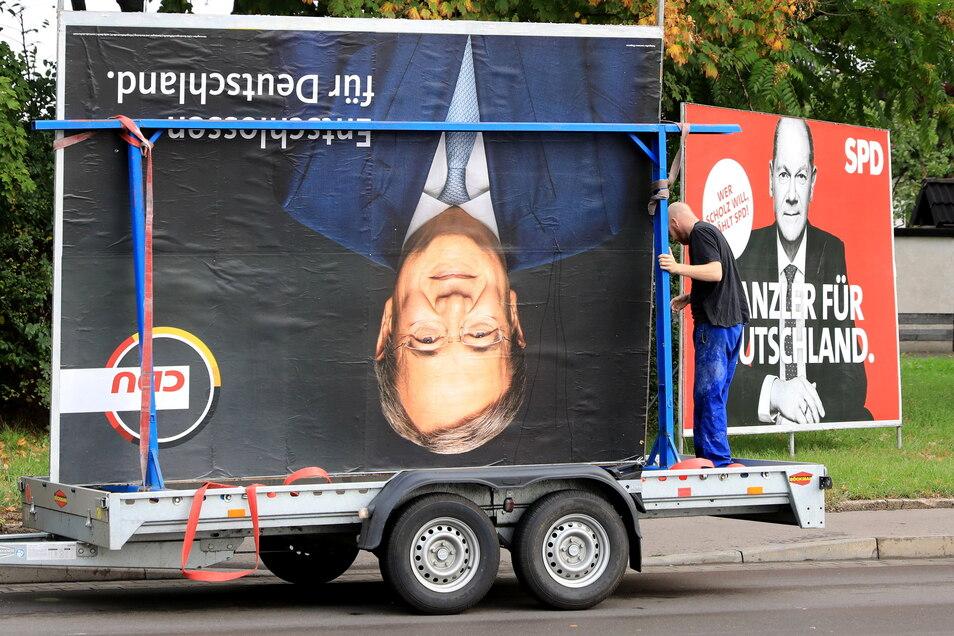 Ein Plakat des Kanzlerkandidaten der Union, Armin Laschet, wird abgebaut. Dabei zeigt es nach unten. Im Hintergrund ein Porträt des SPD-Kandidaten Olaf Scholz.