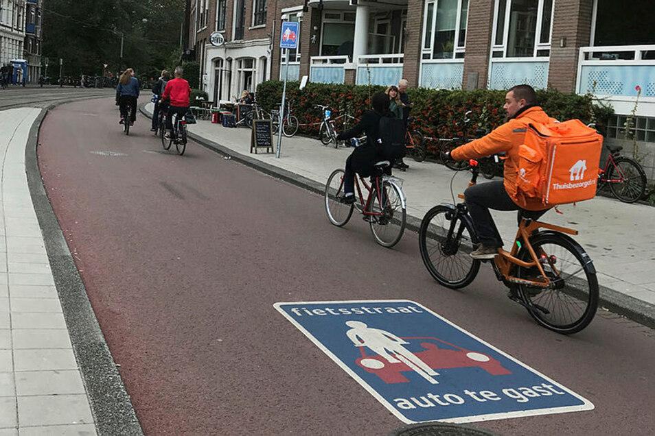 """Radfahrer sind in Amsterdam auf einer """"Fietsstraat"""" unterwegs, einer Straße für Radfahrer, auf der Autos nur zu Gast sind. Fiets heißt Fahrrad."""