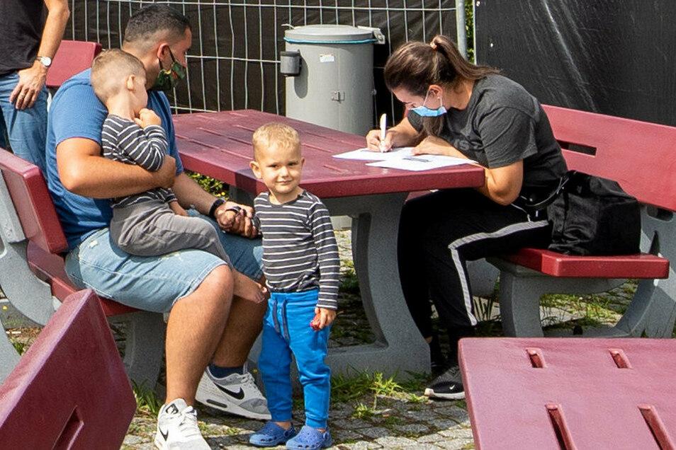 Familie Murati aus Wolfsburg beim Ausfüllen der Formulare. Die Vier haben Verwandte im Risikostaat Kosovo besucht. Deshalb ist der Coronatest für sie nun Pflicht.