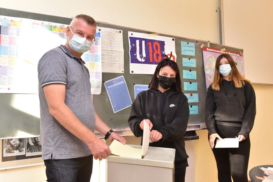 Mia und Michaela (hinten) haben sich am Berufsschulzentrum in Dippoldiswalde an der U18-Wahl beteiligt und geben bei Ronny Wenzel von Pro Jugend ihren geheim ausgefüllten Stimmzettel ab.