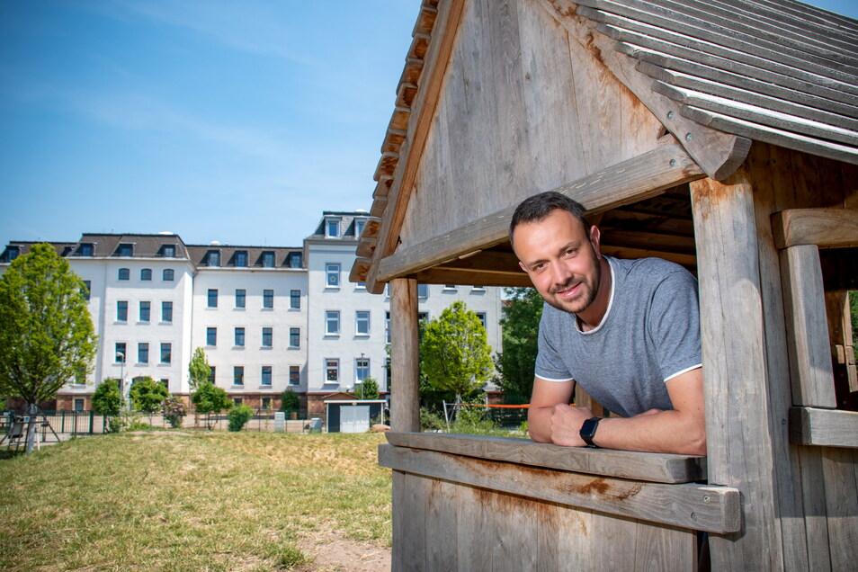 Mario Greif, Leiter der Kita Kleeblatt, schaut aus einem Spielhaus des neuen Pausenhofs der Kunzemannschule. Die Kita, die direkter Nachbar und auch Hort der Grundschule ist, darf die Spielmöglichkeit ebenfalls nutzen.