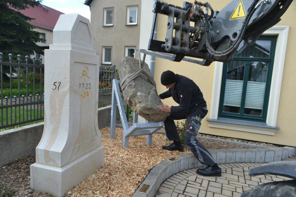 Quersas Ortsvorsteher Marcel Nicke platziert den kursächsischen Viertelmeilenstein auf einem Metallrahmen vorm Dorfgemeinschaftshaus.