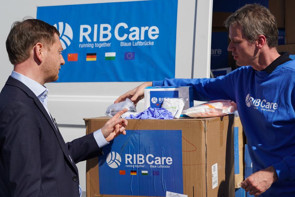 Michael Kretschmer (CDU, l) nimmt von Michael Woitag, Vorstand der RIB Information Technologies AG Deutschland, eine Hilfslieferung von medizinischen Hilfsgütern entgegen.