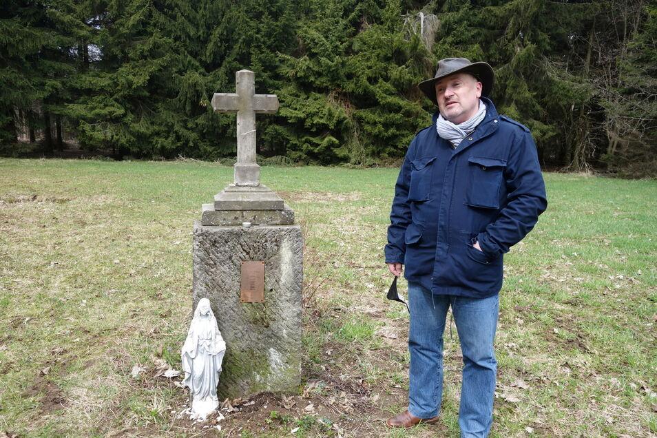 Wochenendhäusler Jaroslav Cervík steht am Kreuz, das der Bergverein für die ehemaligen Bewohner von Adolfov (Adolfsgrün) anstelle des ehemaligen Friedhofs errichten ließ.