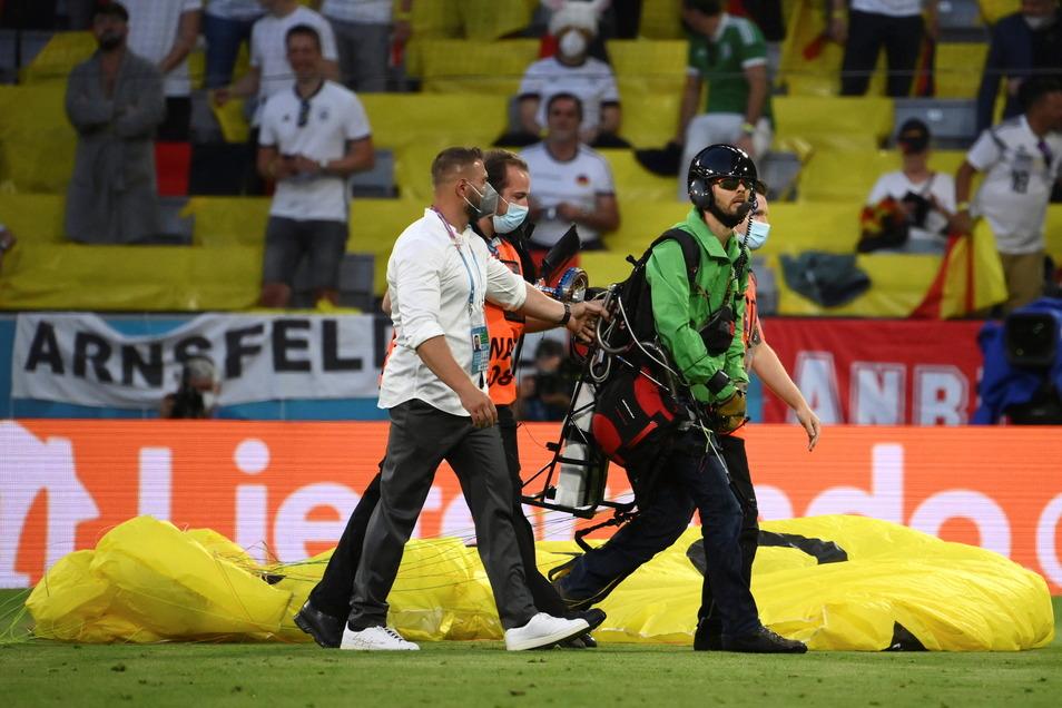 Sicherheitskräfte führen den Mann nach seiner Landung vom Spielfeld.