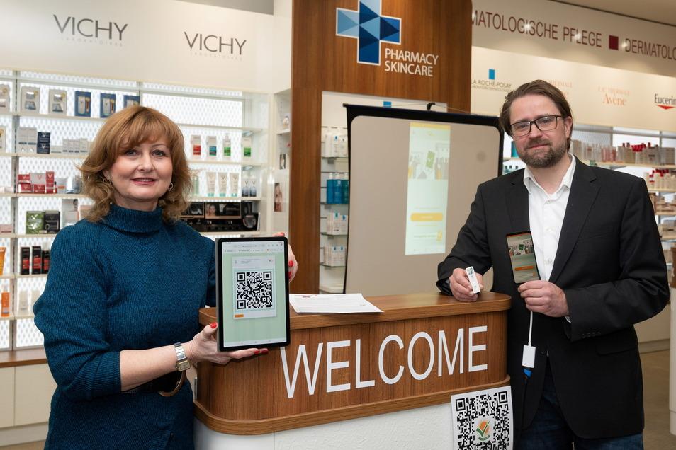 Kathleen Parma und Jörg Meißner stellen in der City-Apotheke am Goldenen Reiter die neue Funktion der App vor. Apotheker können Schnelltest-Ergebnisse ihrer Kunden in die App übermitteln.