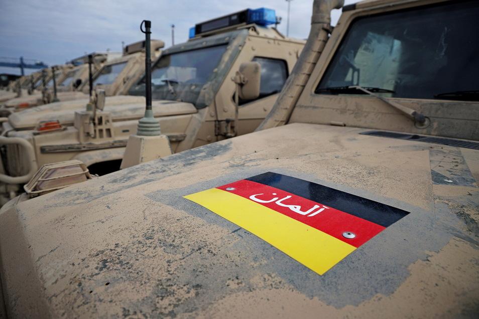 Auf ein paar der mit Schlämmkreide getarnten Geländewagen klebt noch die Flagge der deutschen ISAF-Truppen in Afghanistan.