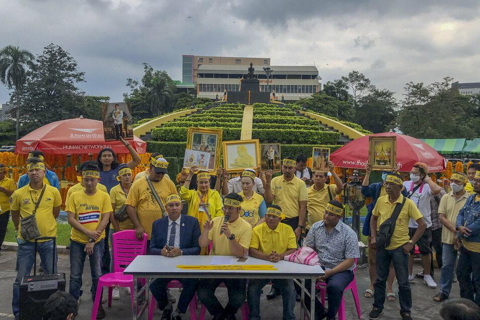 Demonstranten tragen gelbe Kleidung und halten Abbildungen des thailändischen Königs Maha und der Königin Suthida bei einem Protest, um ihre Loyalität für die Institution unter Beweis zu stellen.