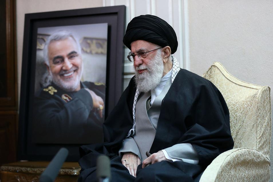 Ajatollah Ali Chamenei, Religionsführer des Iran, sitzt neben einem Foto des getöteten Ghassem Soleimani. Er drohte den USA mit Vergeltung.