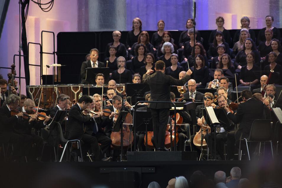 Die Berliner Philharmoniker unter der Leitung des Chefdirigenten Kirill Petrenko (M) spielen ein Konzert am Brandenburger Tor. So nah beieinander sitzen können die Musiker in Corona-Zeiten nicht mehr.
