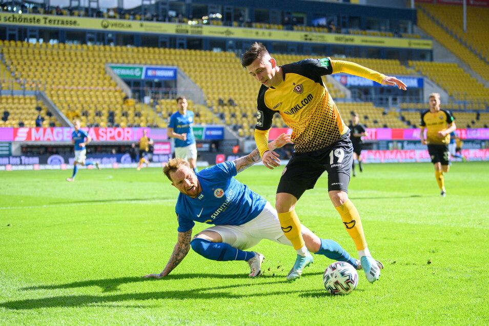 Rostocks Jan Löhmannsröben rutscht aus, Dynamos Jonathan Meier erobert den Ball.