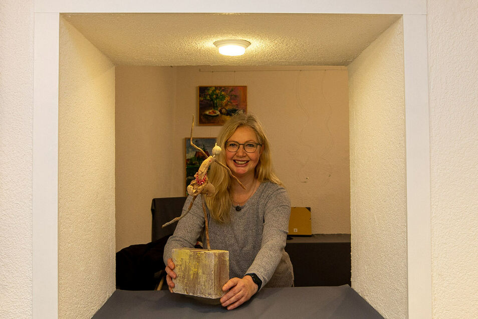 """Brigitta M. Arnold mit ihrer """"Tänzerin aus Treibholz"""", die sie ins ehemalige Fenster stellt."""