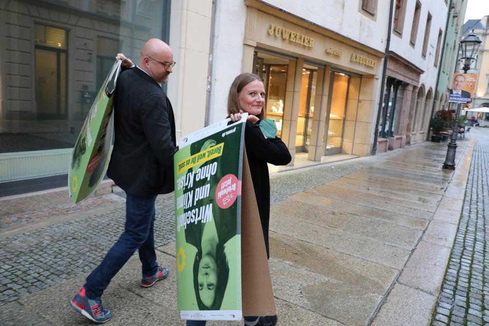 Wolfgang Wetzel, (l) Spitzenkandidat der Grünen und Christin Furtenbacher, Landesvorstandssprecherin der Grünen in Sachsen, laufen mit Wahlplakaten durch Zwickau.