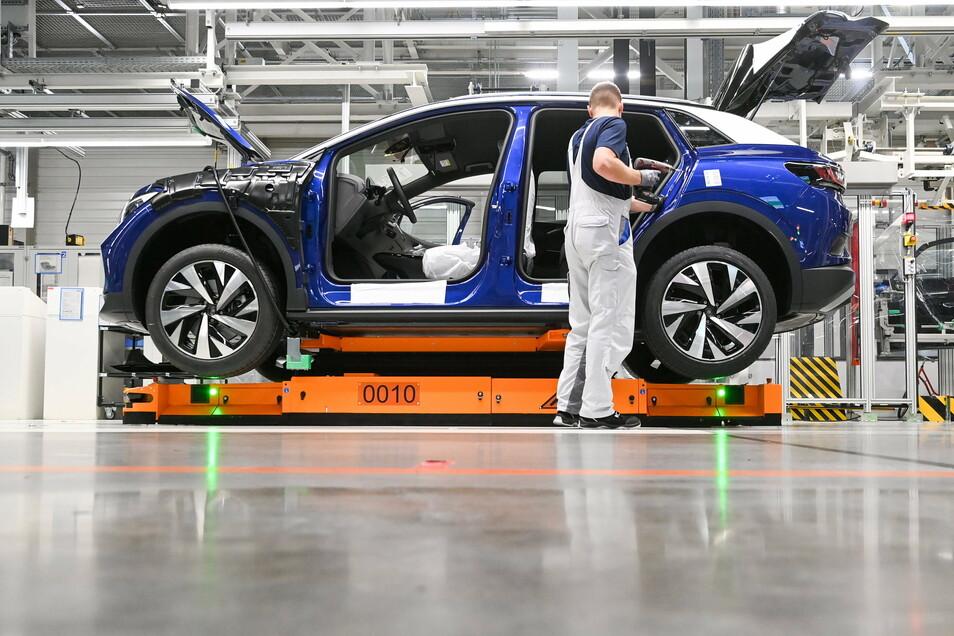 Ein Mitarbeiter im Volkswagenwerk in Zwickau komplettiert einen VW ID.4. Politikern zufolge muss auch das Wirtschaftsleben heruntergefahren werden, sollte sich die Infektionslage in Deutschland nicht entspannen.