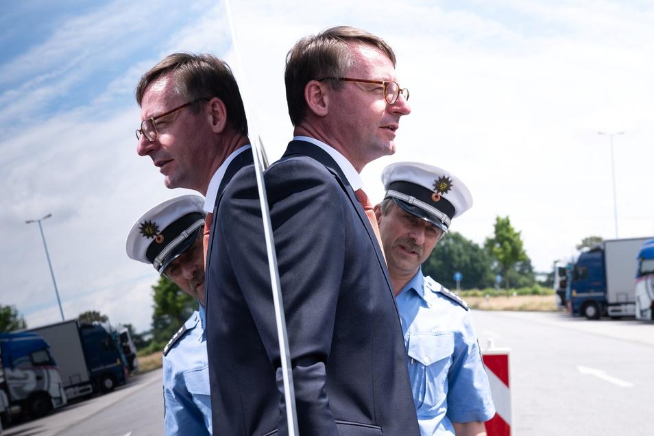 Sachsens Innenminister Roland Wöller (CDU), der sich hier in der Scheibe eines Polizeiautos spiegelt, präsentierte an der A 4 bei Bautzen das neue System, mit dem die Beamten gezielt Lkw-Fahrer herauswinken können, um Verstöße zu ahnden.