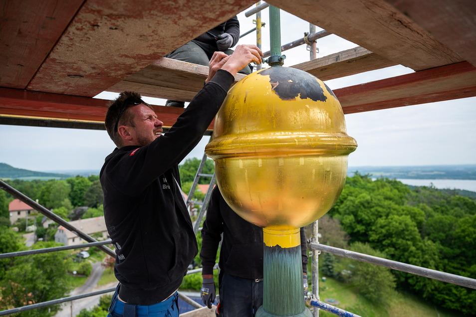 Ein Mitarbeiter einer Görlitzer Dachdeckerei beginnt mit der Demontage der Turmkugel auf dem Kirchturm in Jauernick-Buschbach.