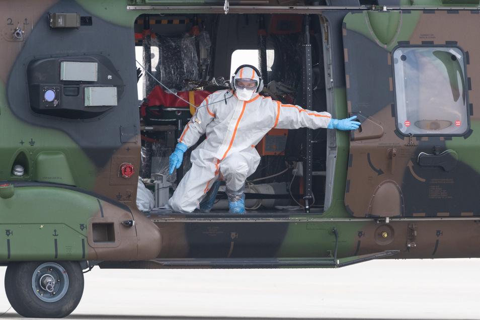 Ein Besatzungsmitglied in Schutzkleidung öffnet die Tür des militärischen Transporthubschraubers vom Typ NH90 nach der Landung auf dem Flughafen Dresden. Zwei schwer am Coronavirus erkrankte Patienten waren aus Bourscheid in der Region Grand Est zur Behan