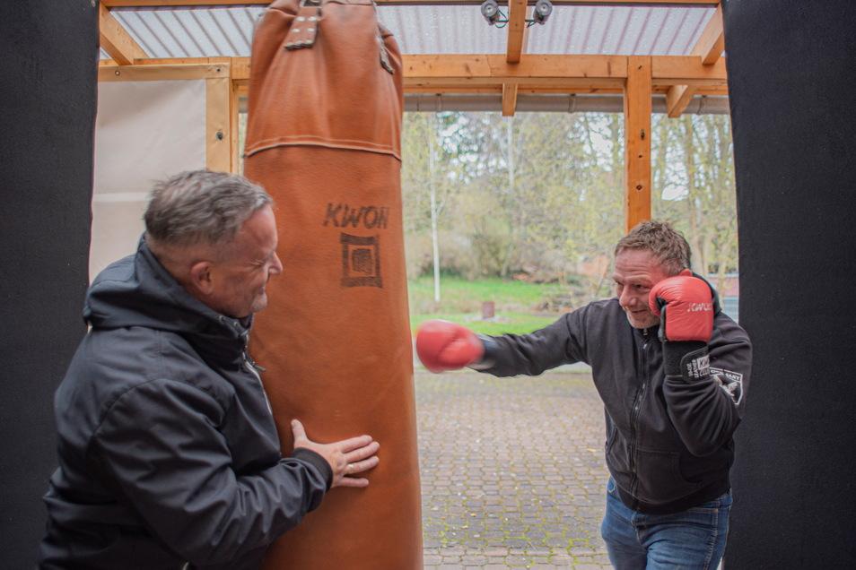 Vorstand Jens Skarupski (r.) vom Tomogara-Zentrum in Kamenz hat sich den frisch montierten Boxsack im Außengelände vorgenommen. Jan Geppert hält gegen. Das Sportzentrum baut jetzt Übungsplätze im Freien auf.