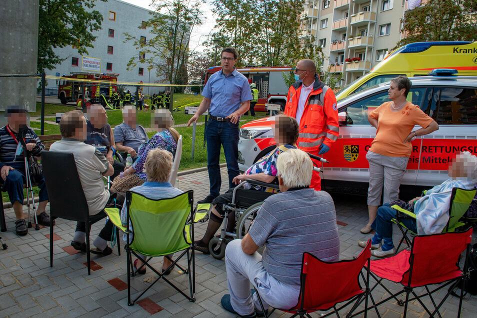 Oberbürgermeister Sven Liebhauser spricht zu den geretteten Bewohnern, die auf einem Parkplatz neben dem Haus warten.
