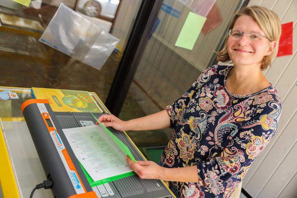 Katrin Stenker schlägt in Roßwein in einem Schaufenster des früheren Spielwarengeschäfts am Markt Schulbücher ein. Dieser Service wäre sonst mit der Schließung der Spielwelt verloren gegangen.