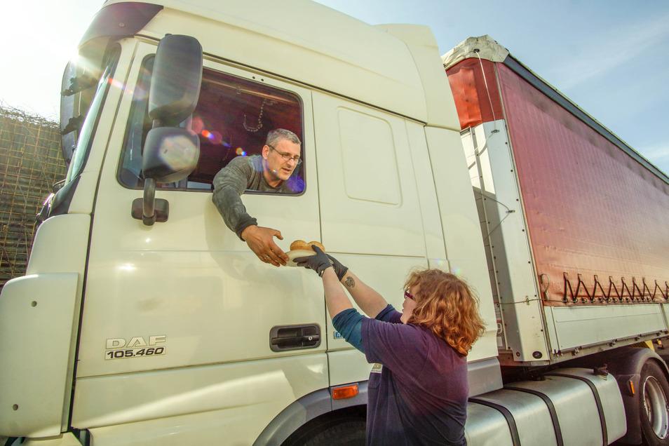 Julia Gornig verteilt Bockwurst und Brötchen an einen Lastwagenfahrer.