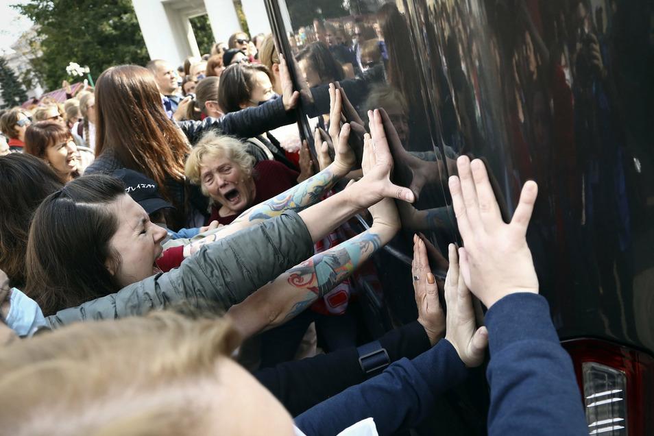 Frauen blockieren bei einer Kundgebung der belarussischen Opposition gegen die Ergebnisse der Präsidentenwahl ein Polizeifahrzeug.