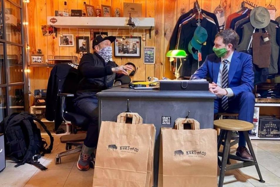"""Aussprache auf Augenhöhe: Ministerpräsident Michael Kretschmer auf Überraschungsbesuch bei Sven Ehmann in seinem Geschäft für """"Handelsgüter und Tätowierungen"""" im Barockviertel."""