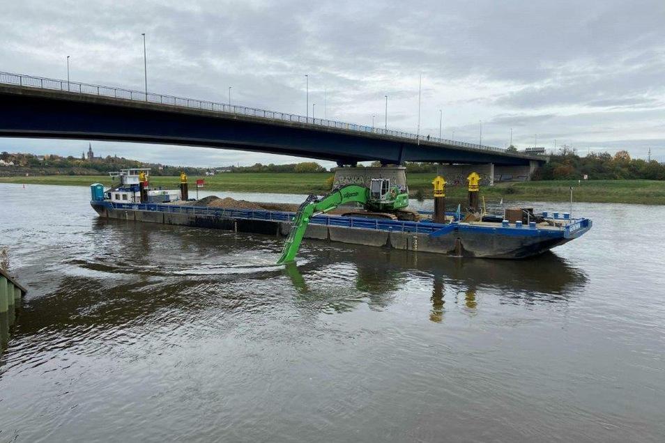 Von diesem Schiff aus wird an der Flügelwegbrücke in Dresden der Elbgrund über dem Abwassertunnel abgebaggert. Dort wird unter Wasser ein Schutzstreifen hergestellt.