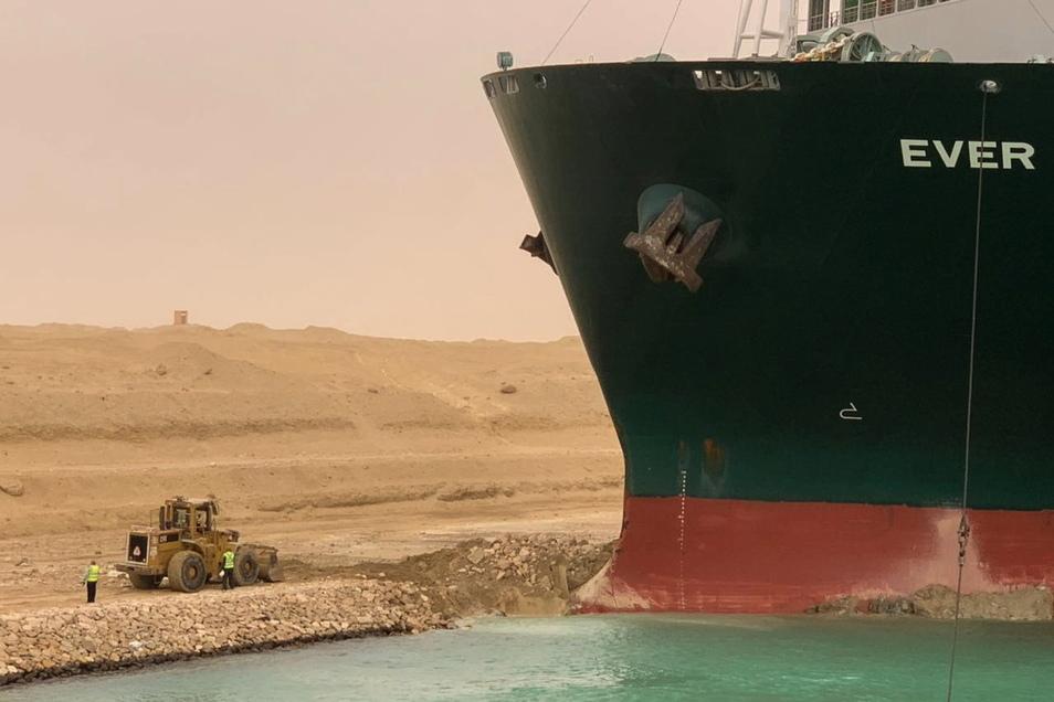 Ein Bagger versucht, das vordere Ende des Containerschiffs zu befreien. Das Schiff hatte sich auf dem Weg von China nach Rotterdam im Kanal seitlich gedreht.