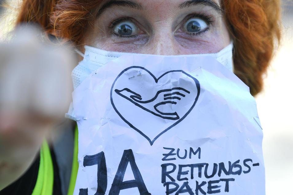 """Eine Lufthansa-Flugbegleiterin trägt während einer Demonstration vor der Lufthansa-Zentrale am Frankfurter Flughafen einen Mundschutz mit der Aufschrift """"Ja zum Rettungspaket""""."""
