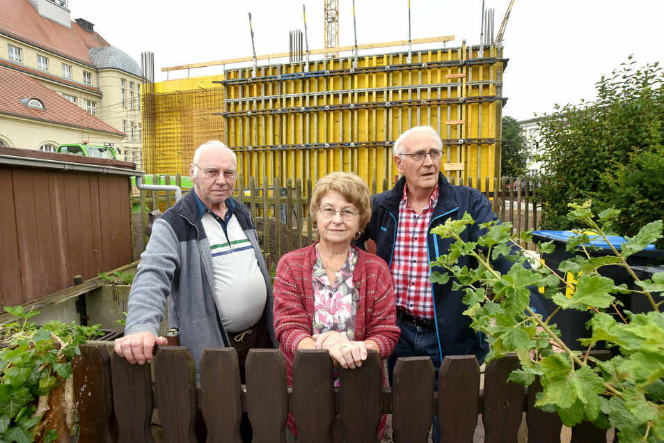 Rosine und Werner Meißner, hier mit ihrem Freund Günter Rößner (r.), haben von ihrem Garten künftig Ausblick auf eine graue Wand: die neue Sporthalle in der Zittauer Weinau.
