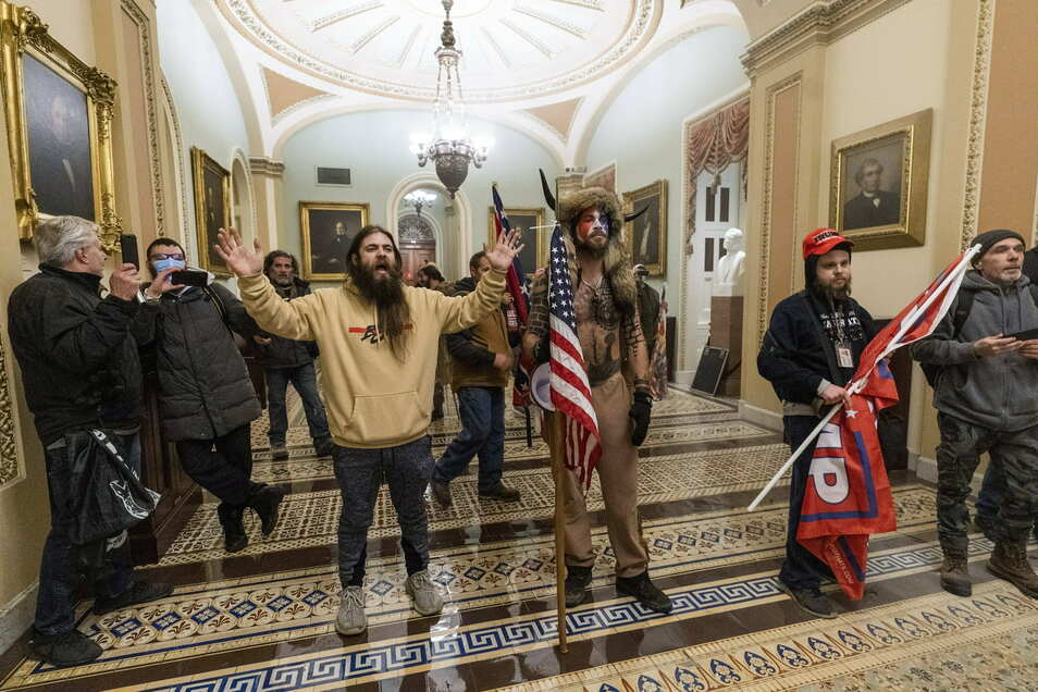 Unterstützer des abgewählten US-Präsidenten Trump stehen vor Polizisten auf dem Gang vor der Senatskammer im Kapitol.