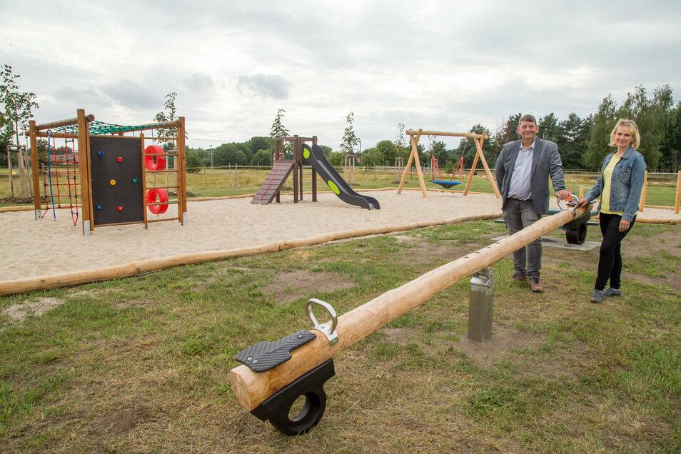 """Bürgermeister Uwe Blättner und Uta Waschnick stehen vor dem neuen Spielplatz im Wohngebiet """"Heideblick"""" in Mücka. Am Sonntagnachmittag wird er eingeweiht."""