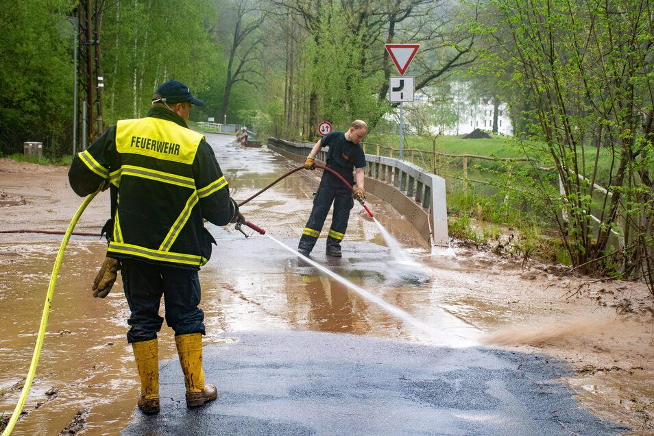Nach der Überschwemmung in der Nacht beseitigen Harthaer Feuerwehrleute den Schlamm von der Straße in Steina.