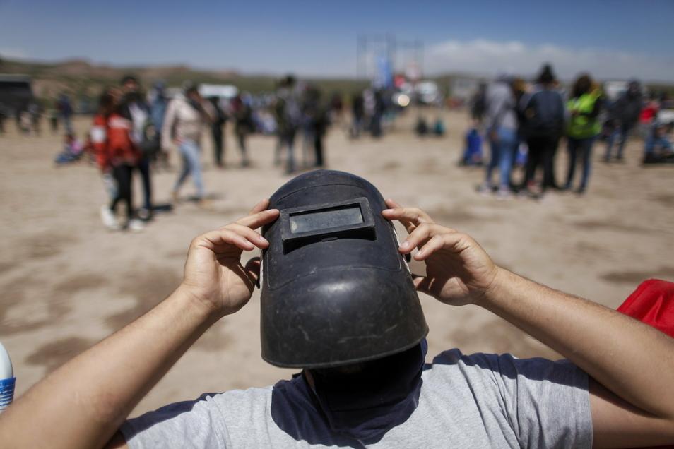 Mit einer Schweißermaske als Schutz wartet ein Mann auf eine totale SonnenfinsternisFoto: Natacha Pisarenko/AP/dpa +++ dpa-Bildfunk +++ Foto: AP