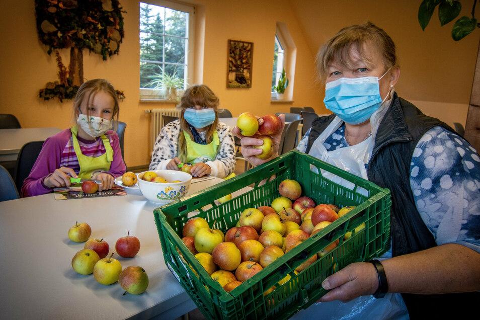 Fürs Foto helfen die Viertklässlerinnen Friederike und Johanna (beide 10) Andrea Pampel beim Obstschneiden. Die technische Mitarbeiterin der Grundschule Sitten bereitet die Obstteller sonst allein zu – coronabedingt.