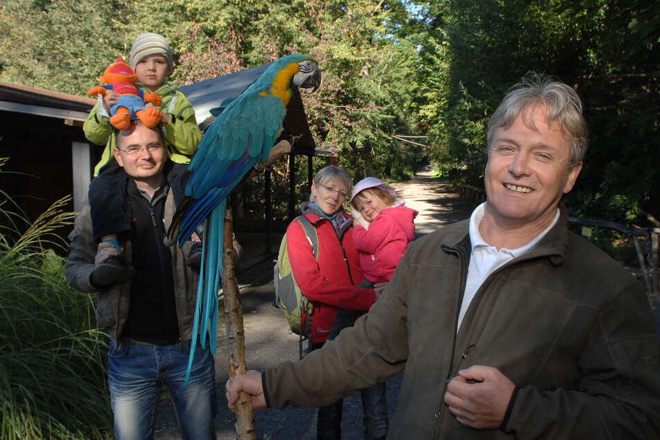 """Die Urlauber haben einen wichtigen Anteil an den Besuchen. Hier begrüßen Tierparkdirektor Bernd Großer und Ara-Dame """"Lora"""" Familie Fischer aus Bad Schandau, die in Waltersdorf weilten und natürlich einen Abstecher in den Tierpark machten."""