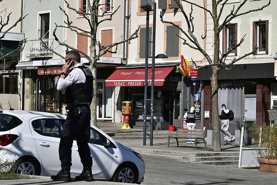 Ein Polizist telefoniert und im Hintergrund ermittelt die Spurensicherung (r) am Tatort nachdem ein Mann mehrere Personen mit einem Messer angegriffen hat.