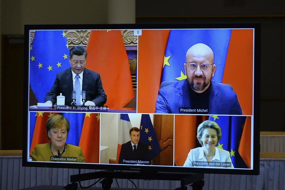 Ein Bildschirm zeigt Xi Jinping (oben l-r), Präsident von China, Charles Michel, Präsident des Europäischen Rates, Bundeskanzlerin Angela Merkel (unten l-r), Emmanuel Macron, Präsident von Frankreich, und Ursula von der Leyen, Präsidentin der Europä