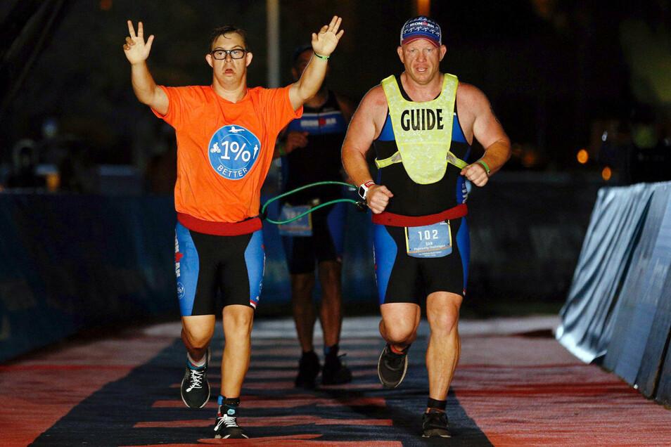 An der Seite seines Trainers Daniel Grieb läuft Chris Nikic (l) mit erhobenen Armen ins Ziel des Ironman Florida.