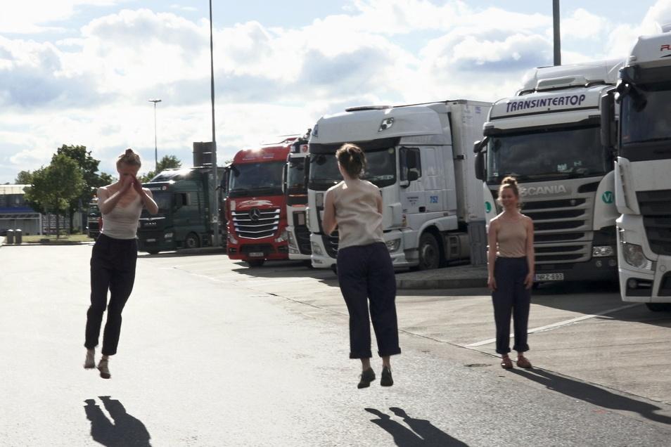 """Die Tänzerinnen auf dem Rastplatz wirken nur auf den ersten Blick deplatziert – es geht auch ihnen um """"Transit""""."""