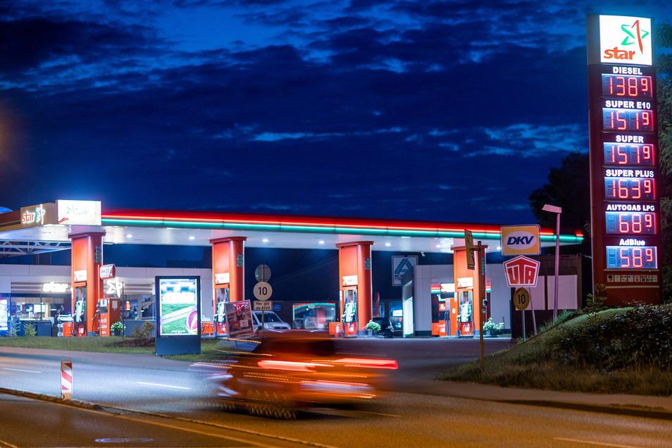 Ein Auto fährt vor Sonnenaufgang an einer beleuchteten Tankstelle vorbei. Die Spritpreise sind zuletzt stark gestiegen.
