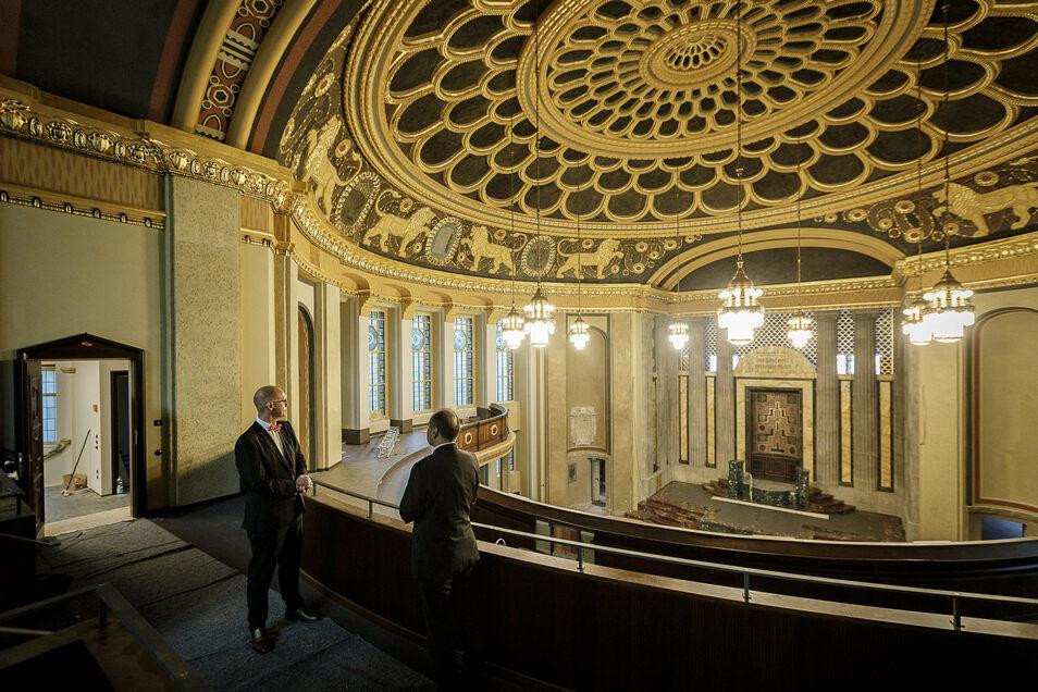 Sparkassenvorstand Michael Bräuer (links) und Oberbürgermeister Octavian Ursu stehen in der ehemaligen Synagoge und schauen sich die neuen Leuchter an.